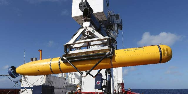 In this Thursday, April 17, 2014 photo provided by the Australian Defense Force the Phoenix International Autonomous Underwater Vehicle (AUV) Artemis is craned over the side of Australian Defense Vessel Ocean Shield before launching the vehicle into the southern Indian Ocean in the search of the missing Malaysia Airlines Flight 370.  Up to 11 aircraft and 12 ships continue to scan the ocean surface for debris from the Boeing 777 that disappeared March 8 en route from Kuala Lumpur to Beijing with 239 people on board. (AP Photo/Australian Defense Force, Bradley Darvill) EDITORIAL USE ONLY