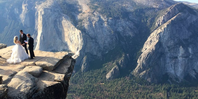 A couple get married at Taft Point in California's Yosemite National Park on Thursday, Sept. 27, 2018.