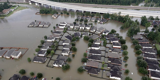 Homes are surrounded by floodwaters from Tropical Storm Harvey Tuesday, Aug. 29, 2017, in Spring, Texas.