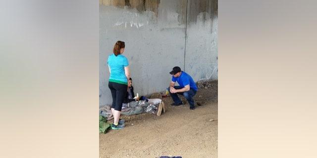 Veteran Kyle Cornwell and a volunteer speaking with a homeless veteran.