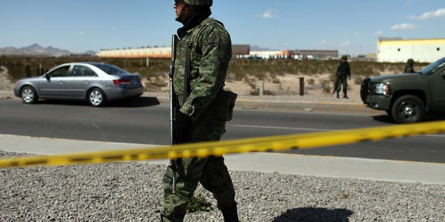JUAREZ, MEXICO - MARCH 24:  A member of the Mexican military police keeps guard over a car, pictured at left, bearing a bullet-ridden body on March 24, 2010 in Juarez, Mexico. Secretary of State Hillary Rodham Clinton, Defense Secretary Robert Gates, and Homeland Security Secretary Janet Napolitano all visited Mexico yesterday for discussions centered on Mexico's endemic drug-related violence. The border city of Juarez, Mexico has been racked by violent drug-related crime recently and has quickly become one of the most dangerous cities in the world in which to live. As drug cartels have been fighting over ever-lucrative drug corridors along the United States border, the murder rate in Juarez has risen to 173 slayings for every 100,000 residents. President Felipe Calderon's strategy of sending 7000 troops to Juarez has not mitigated the situation. With a population of 1.3 million, 2,600 people died in drug-related violence last year and 500 so far this year, including two Americans recently who worked for the U.S. Consulate and were killed as they returned from a child's party.  (Photo by Spencer Platt/Getty Images)