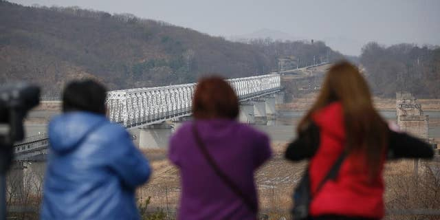 FILE - In this Friday, March 18, 2016, file photo, visitors look at the northern side at the Imjingak Pavilion near the border with North Korea, in Paju, South Korea.  North Korea fired a short-range projectile from an area near its eastern coast on Tuesday, March 29, 2016, South Korean officials said, in what appears to be another weapons test seen as a response to ongoing military drills between Washington and Seoul.(AP Photo/Lee Jin-man)