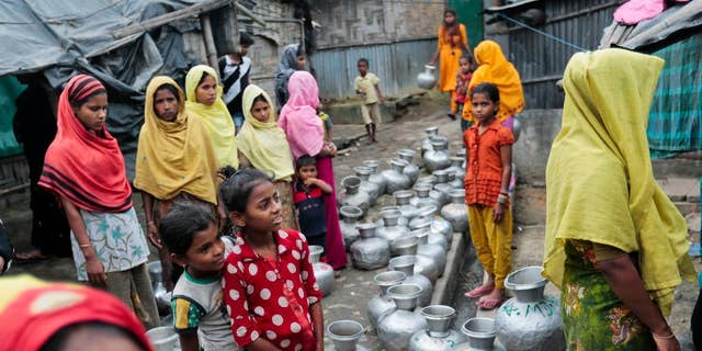 In this Dec. 3, 2016, file photo, Rohingya women and children wait to collect water at the Leda camp, an unregistered camp for Rohingya in Teknaf, near Cox's Bazar, a southern coastal district south of Dhaka, Bangladesh.
