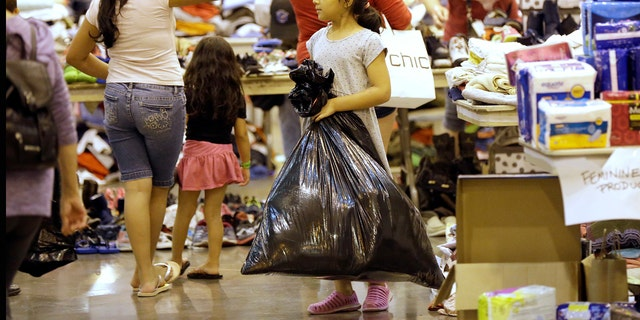 An evacuated child carries donated supplies in a trash bag at a shelter.