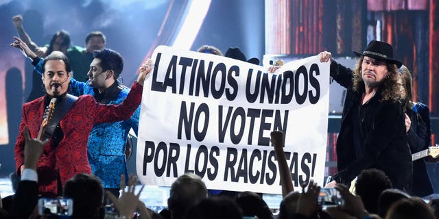 LAS VEGAS, NV - NOVEMBER 19:  Members of the music groups Mana and Los Tigres Del Norte hold up a sign onstage during the 16th Latin GRAMMY Awards at the MGM Grand Garden Arena on November 19, 2015 in Las Vegas, Nevada.  (Photo by Frazer Harrison/Getty Images for LARAS)