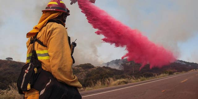 Upland Fire Capt. Joe Burna watches as a tanker drops fire retardant to stop a wildfire from jumping over Highway 94 near Potrero, Calif., on Monday, June 20, 2016. (Hayne Palmour IV/San Diego Union-Tribune via AP)
