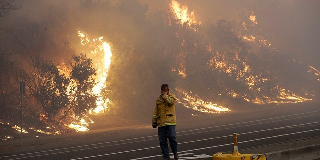 A firefighter covers his eyes as he walks past a burning hillside in Santa Rosa, Calif., Monday, Oct. 9, 2017.