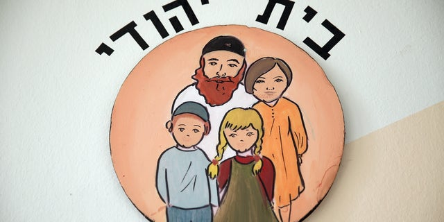 """BERLIN, GERMANY - NOVEMBER 08:  An inscription in Hebrew reads: """"Jewish Home"""" above a picture of a traditional Jewish family at the Or Avner traditional Jewish school during a visit by Ashkenazi Chief Rabbi of Israel David Lau on November 8, 2013 in Berlin, Germany. A recent study released by the European Union Fundamental Rights Agency concludes that Jews across Europe fear rising anti-semitism today across the region. Germany is currently commemorating the 75th anniversary of the Kristallnacht pogroms, during which Nazi gangs burned down synagogues, smashed shops and looted residences across Germany and Austria in a fury of anti-semitic violence in 1938. Persecution of Jews was a central component of Adolf Hitler's rise to power.  (Photo by Sean Gallup/Getty Images)"""