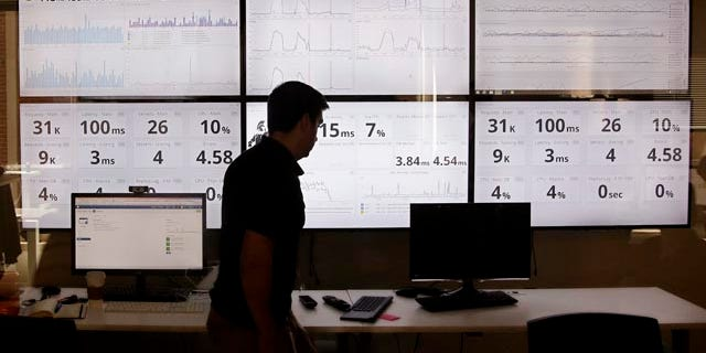 Sept. 9, 2015: An employee in the software development department of DraftKings, a daily fantasy sports company, walks past screens displaying the company's online system stats in Boston. (AP Photo/Stephan Savoia)