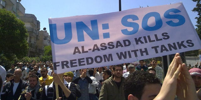May 6: In this citizen journalism image made on a mobile phone and acquired by the AP, Syrian anti-government protesters carry a banner during a rally in the central city of Homs, Syria.