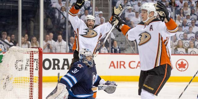 Anaheim Ducks left wing Patrick Maroon (19) and right wing Corey Perry (10) celebrate Perry's goal against Winnipeg Jets goalie Ondrej Pavelec (31) during the second period of Game 3 of the opening round of the Stanley Cup NHL hockey playoffs, Monday, April 20, 2015, in Winnipeg, Manitoba. Anaheim defeated Winnipeg 5-4 in overtime, taking a 3-0 series lead. (Michael Goulding/The Orange County Register via AP)