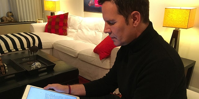 Feb. 4, 2018: Juan Carlos Cruz reads from his tablet during an interview with The Associated Press in Philadelphia.