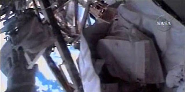 Nov. 18: Astronaut Heidemarie Stefanyshyn-Piper reaches for the tool bag she later lost during a spacewalk.