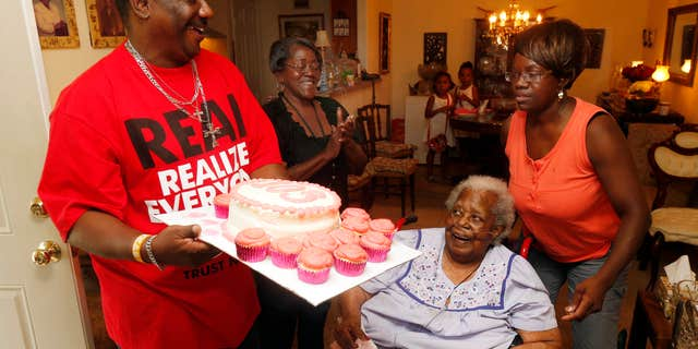 """FILE- In this July 25, 2015, file photo, Terrance Jackson, left, Doris Ware, second from left, and Beverly Booker, right, sing """"Happy Birthday To You"""" to Bernice Williams, seated, as she celebrates her 103rd birthday in the Mill City neighborhood of Dallas."""