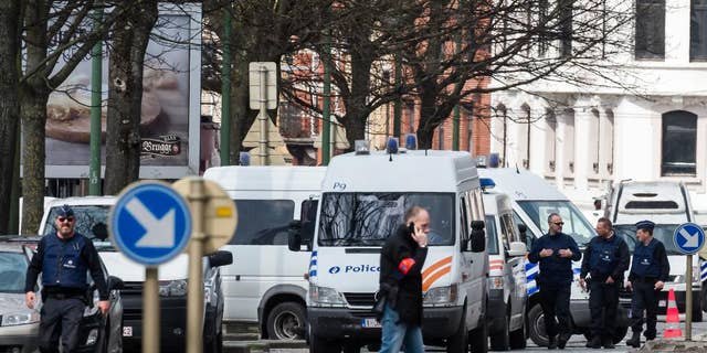 Police secure an area during a house search in the Etterbeek neighborhood in Brussels on Saturday April 9, 2016. The arrest Friday of six men suspected of links to the Brussels bombings, including the last known fugitive in last year's Paris attacks, raised new questions about the extent of the Islamic State cell believed to have carried out the intertwined attacks that left 162 people dead in two countries. (AP Photo/Geert Vanden Wijngaert)