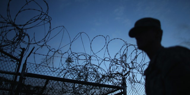 GUANTANAMO BAY, CUBA - JUNE 27:  (EDITORS NOTE: Image has been reviewed by the U.S. Military prior to transmission.) A Public Affairs Officer escorts media through the currently closed Camp X-Ray which was the first detention facility to hold 'enemy combatants' at the U.S. Naval Station on June 27, 2013 in Guantanamo Bay, Cuba.The U.S. Naval Station at Guantanamo Bay, houses the American detention center for 'enemy combatants'. President Barack Obama has recently spoken again about closing the prison which has been used to hold prisoners from the invasion of Afghanistan and the war on terror since early 2002.  (Photo by Joe Raedle/Getty Images)