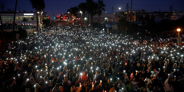 People hold candles and flashlights into the air during a memorial for Rachael Parker and Sandy Casey, Manhattan Beach city employees and victims of the October 1st Las Vegas Route 91 music festival mass shooting, in Manhattan Beach, California, U.S., October 4, 2017.