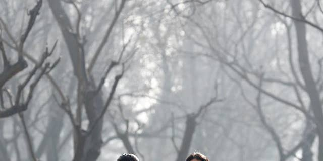 Chinese women wearing masks to protect themselves from air pollution walk through Ritan Park shrouded by dense smog in Beijing three years ago. (AP Photo/Andy Wong, File)