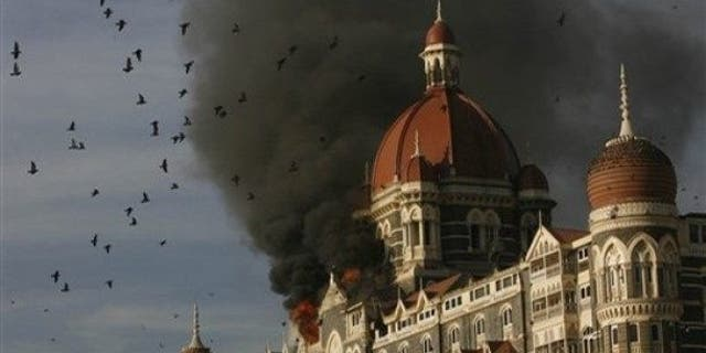 In this Nov. 27, 2008 file photo, pigeons fly as the Taj Hotel continues to burn during terror attacks in Mumbai, India. Indian Prime Minister Manmohan Singh said Tuesday, Jan. 6, 2009, that he did not believe the November Mumbai attacks gunmen were acting alone, and Pakistani state agencies must have had a hand in the attacks. (AP Photo/Gautam Singh, File)