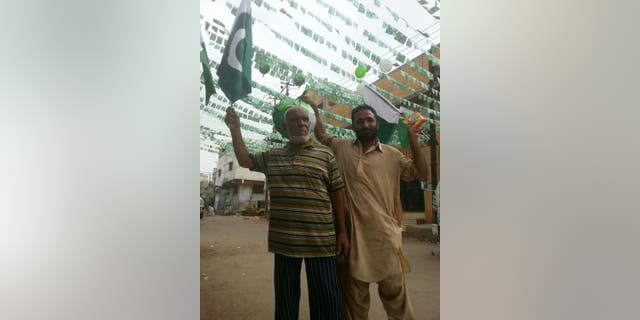 Locals in Lyari, Karachi, waving Pakistan flags.