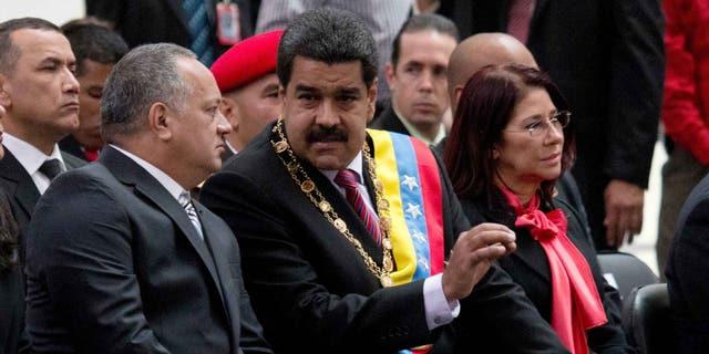 El presidente venezolano Nicolás Maduro, al centro, habla con Diosdado Cabello, presidente de la Asamblea Nacional, izquierda, durante una ceremonia para conmemorar el 185to aniversario de la muerte del héroe independentista Simón Bolivar en Caracas, Venezuela, el jueves 17 de diciembre de 2015. La mujer a la derecha es la primera dama Cilia Flores.