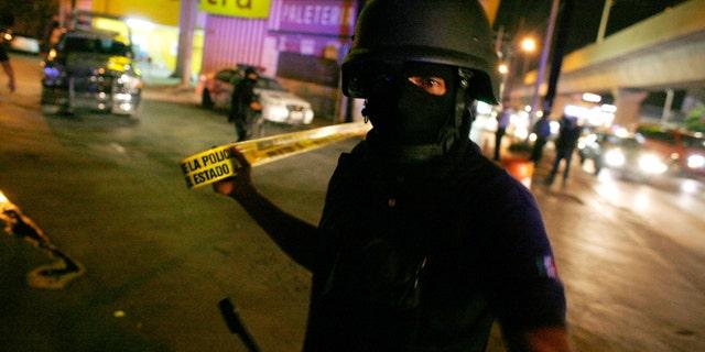 File photo. June 11, 2010: A Mexican policeman cordons off a crime scene.
