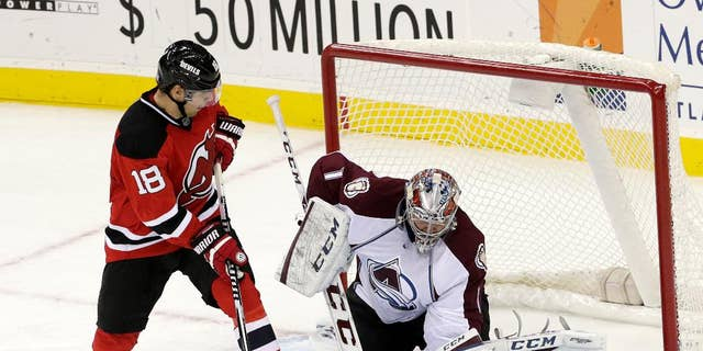 Colorado Avalanche goalie Semyon Varlamov, right, of Russia, gloves the puck as New Jersey Devils right wing Steve Bernier (18) looks for a rebound during the third period of an NHL hockey game, Saturday, Nov. 15, 2014, in Newark, N.J. The Avalanche won 3-2. (AP Photo/Julio Cortez)