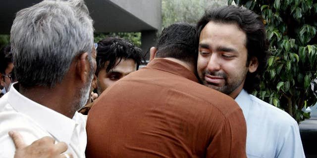 In this May 2013 file photo, people comfort Musa Gilani, right, the brother of Ali Haider Gilani who was kidnapped in Multan, Pakistan.