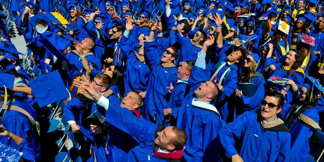 FILE - In this May 31, 2014 file photo, graduates throw their caps in the air in triumph at the University of Delaware's commencement ceremony in Newark, Del. Is someone in your family graduating from college this year? If so, here are a few things to keep in mind that might preserve your sanity on commencement day.  (AP Photo/Emily Varisco)