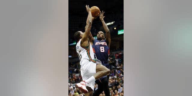 Atlanta Hawks' Shelvin Mack (8) shoots past Milwaukee Bucks' Chris Wright (15) during the first half of an NBA basketball game on Wednesday, April 16, 2014, in Milwaukee. (AP Photo/Morry Gash)
