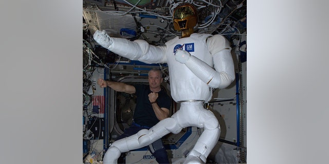 NASA astronaut Steve Swanson poses with the robot Robonaut 2 on the International Space Station after completing an upgrade that gave the robot legs.