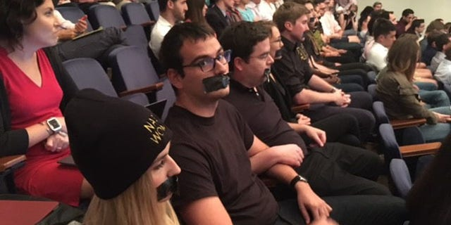 A small group of protesters in all black attire stood up and placed tape over their mouths during the Sessions speech.