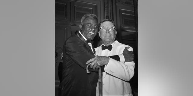 """FILE - In this July 20, 1962 file photo, baseball player Jackie Robinson embraces Branch Rickey in New York. Rickey was general manager of the Brooklyn Dodgers when Robinson was hired. The home area of the late baseball executive Rickey expects increased interest in his southern Ohio roots from his depiction in the movie """"42,"""" in which Harrison Ford plays the man who signed Jackie Robinson to challenge baseball's color line. (AP Photo/File)"""
