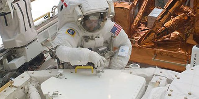 Astronaut Mike Massimino is photographed during extravehicular activity to refurbish and upgrade the Hubble Space Telescope.
