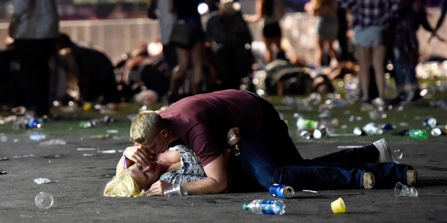 A man lays on top of a woman as others flee the Route 91 Harvest country music festival grounds in October 2017.