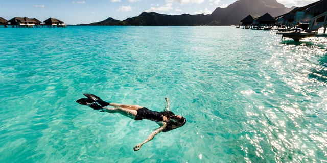 A DSRL photo of a beautiful caucasian young woman floating in clear sea in Bora Bora, French Polynesia. She is wearing a black swimsuit and black fins. The day is sunny with scattered white clouds in the blue sky. At he background is mountain Otemanu, main natural landmark in Bora Bora.