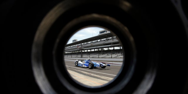 The car driven by Sebastian Saavedra, of Colombia, is seen through a wheel as its pulled through the pit area during practice for the Indianapolis 500 auto race at the Indianapolis Motor Speedway in Indianapolis, Wednesday, May 15, 2013. (AP Photo/Darron Cummings)