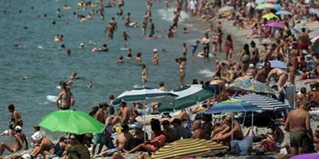 Holidaymakers enjoy the beach of the Promenade des Anglais on a hot summer day in Nice July 23, 2013. REUTERS/Eric Gaillard