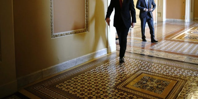 Senate Majority Leader Harry Reid walks to address reporters after the weekly Republican caucus luncheon at the U.S. Capitol in Washington March 11, 2014. (REUTERS/Jonathan Ernst)