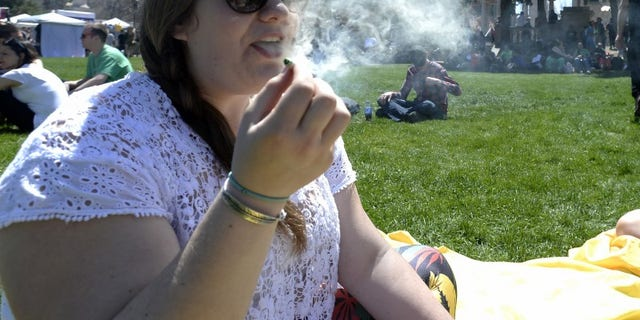 A woman exhales marijuana smoke during the 4/20 Rally at the Civic Center in Denver, Colorado, April 20, 2014. REUTERS/Mark Leffingwell