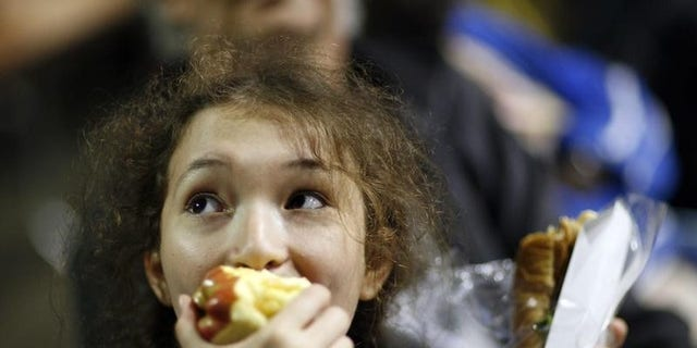 Ayana Kleckner, 15, eats an apple as she waits to take an eye exam at the Remote Area Medical (RAM) health clinic in Inglewood, California August 11, 2009.  REUTERS/Mario Anzuoni