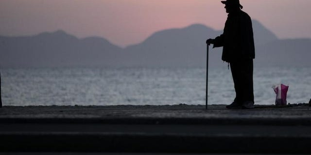 An elderly man stands in Copacabana in Rio de Janeiro September 13, 2011.  REUTERS/Ricardo Moraes