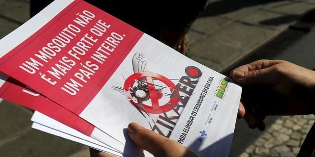 A Brazilian Army soldier shows pamphlets during the National Day of Mobilization Zika Zero in Rio de Janeiro