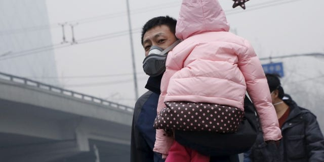 """A man wearing a mask carries his baby on his shoulder amid heavy smog after the city issued its first ever """"red alert"""" for air pollution, in Beijing"""