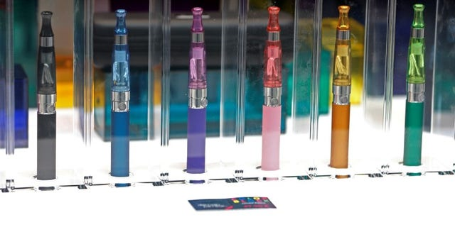 A window display with different colour models of electronic cigarettes is seen in a shop in Paris