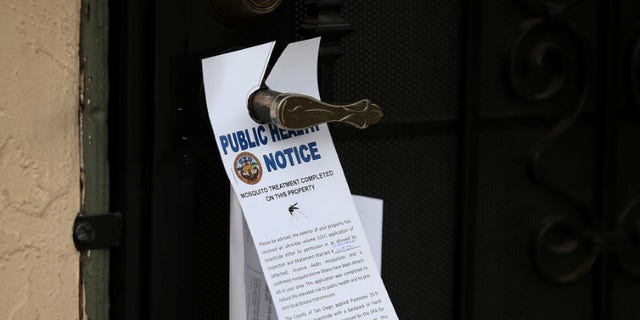 County vector control leave information on door handles as they hand-spraying a neighborhood for adult Aedes mosquitoes after a travel-related case of Zika was confirmed in this the area of San Diego