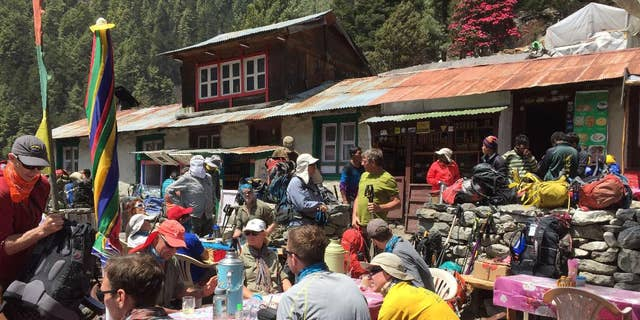 This April 6, 2016 photo shows trekkers at a rest stop north of the village of Namche Bazaar, Nepal. A trek to Everest Base Camp along mountain paths that hug deep gorges offers renewal and a test of mental and physical limits. (AP Photo/Karin Laub)