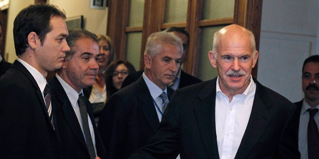 Nov. 8, 2011: Greek Prime Minister George Papandreou, right, gestures as he arrives for a cabinet meeting at the parliament in Athens.