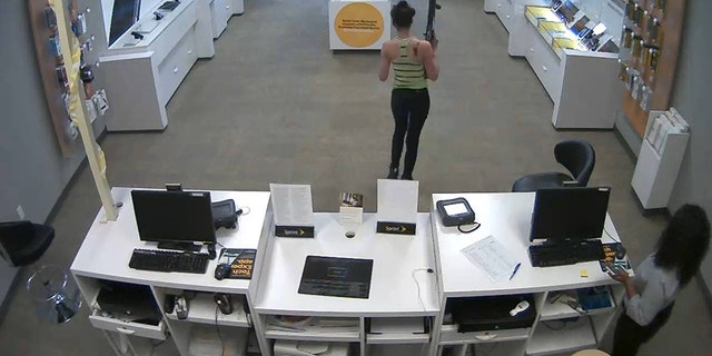 Surveillance of a woman wielding a large rifle during a robbery of a North Carolina Sprint store.