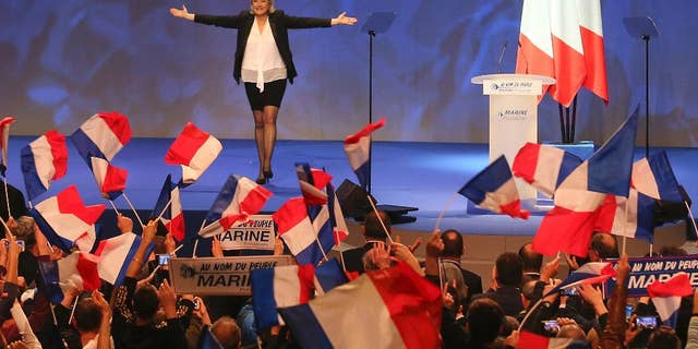 FILE - In this Feb. 26, 2017 file photo, French far-right leader presidential candidate Marine Le Pen gestures at the start of a meeting in Nantes, western France. Marine Le Pen, whose passion for politics and far-right values were forged in the cradle, is making her second bid for the French presidency, hoping this time to break through the ceiling of fear that stopped her father from winning in 2002. (AP Photo/David Vincent, File)